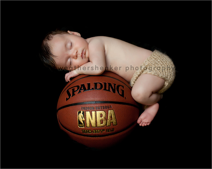 Newborn baby girl on basketball photograph